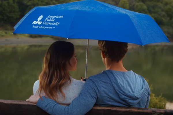 A couple sitting on a bench under an APU umbrella